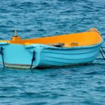 Turquoise and yellow row boat on deep blue water, photo by Meredith Eastwood