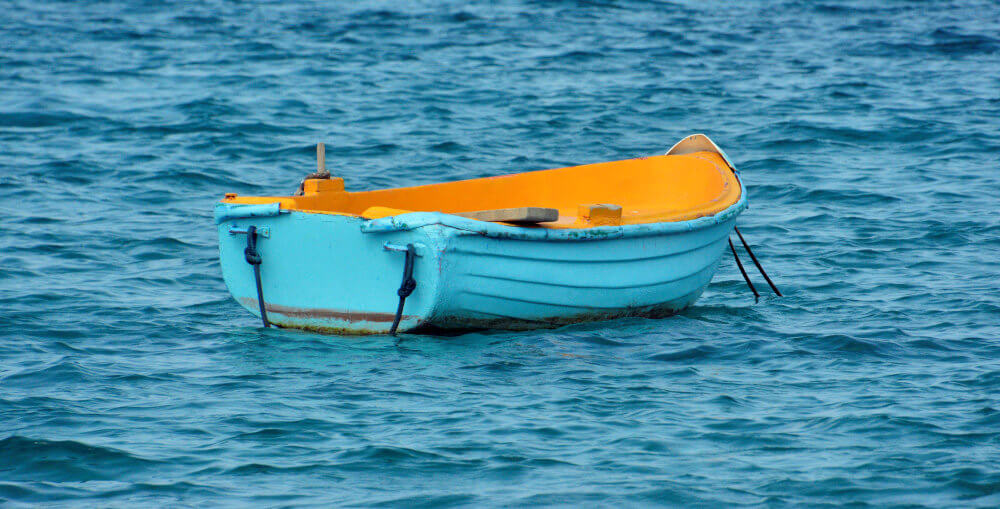 A bright blue wooden rowboat, painted yellow inside, on a beautiful blue sea