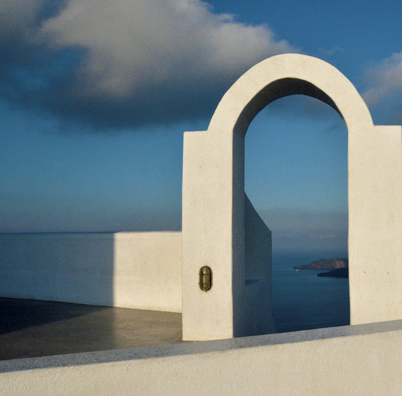A white stucco short wall and tall open window or doorway, looking out over the sea. As if it were on a high balcony.