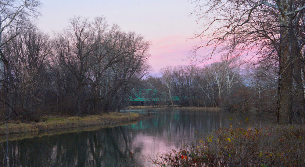Looking over the White River with a pink sunset sky and a green painted metal bridge in the distance