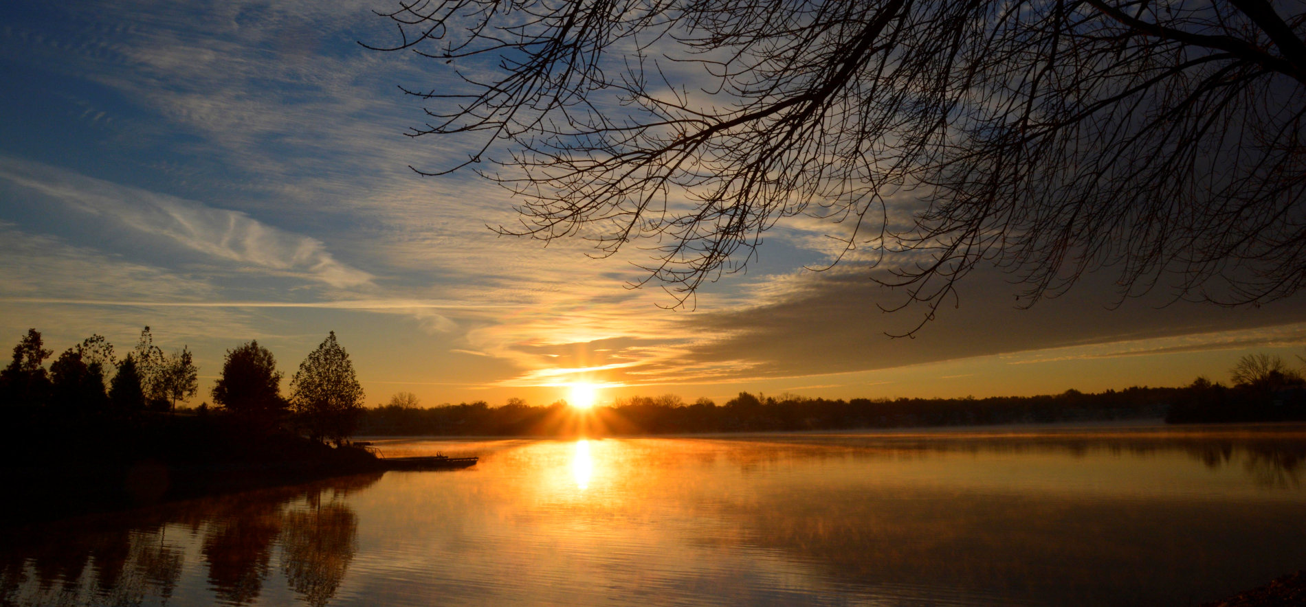 An image of a sunset over a lake with silhouettes of tree branches in the foreground, and whole bare trees off to the left and on the horizon.