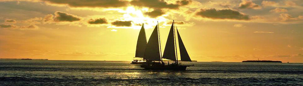 Ship with multiple sails on the sea at sunset